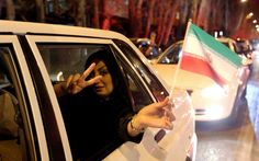 "A woman in a car flashes the ""V for Victory"" sign and waves an Iranian flag as people celebrate on Valiasr street in northern Tehran on April 2, 2015, after the announcement of an agreement on Iran nuclear talks. Iran and global powers sealed a deal on April 2 on plans to curb Tehran's chances for getting a nuclear bomb, laying the ground for a new relationship between the Islamic republic and the West. AFP PHOTO / ATTA KENARE        (Photo credit should read ATTA KENARE/AFP/Getty Images)"