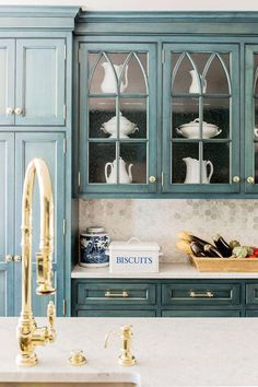 Blue kitchen cabinetry with glass shelves and ceramic dishes on display with gold hardware and tiled backsplash.