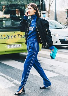 A black bomber jacket is worn over a blue tracksuit with black pumps