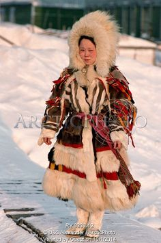 Image of nenets woman wearing a traditional yagushka (coat) made from reindeer & arctic fox skins. yamal, siberia, russia. by ArcticPhoto