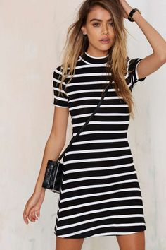 The Stripe Sense Dress is made in a soft ribbed knit and features a mock neck, black and white stripes, short sleeves, fit and flare silhouette.