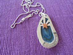 Hängsmycke i silver som skall symbolisera Arizonas flagga