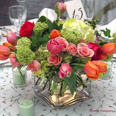 """Modern square vase filled with bright """"spring"""" blossoms in shades of orange,green, and pink. Perfect centerpiece for a party,shower,or wedding. Tulips,viburnum,hydrangea,spray roses, and hypericum berry."""