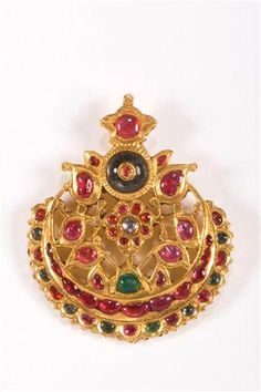 A gold 'tikkah', a pendant headdress set with rubies, emeralds and a diamond