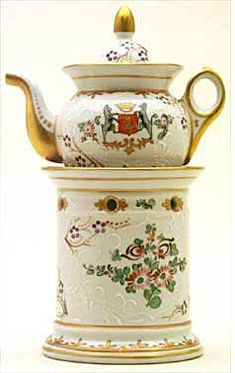 Teapot #466  A charming and unique conventional pot and base; all white background, gold trim with blue,   purple and magenta floral decoration, hinting at an Oriental touch.