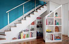 Estante sob a escada: o interessante no projeto da arquiteta Gabriela Marques é a peça dupla que criou para ocupar toda a profundidade de 90 cm. Com rodinhas, parte dela se desloca da parede e expõe mais prateleiras