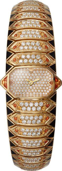 """CARTIER. Montre Haute Joaillerie avec heure apparente """"Serpent Graphique Doré"""", mouvement à quartz, boîte, cadran et bracelet en or jaune 18 carats sertis de 4 grenats pour 0,46 carat, 156 grenats spessartites pour 2,06 carats, 299 diamants taille brillant pour 3,05 carats, décor en laque noire, aiguilles en forme de glaive en or gris rhodié 18 carats, étanche jusqu'à 3 bar (~30 mètres). #Cartier #RésonancesDeCartier #2017 #HauteJoaillerie #HighJewellery #FineJewelry"""