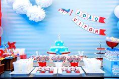 Um tecido azul grampeado em um painel de madeira foi usado para a decoração da festa com tema avião, feita por Liliana Loureiro (www.lilianaloureiro.com.br). Nele foram aplicados bandeirolas, impressas e recortadas, e pompons de papel de seda