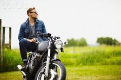 Portrait of stylish young man sitting on motorcycle with camera in ...