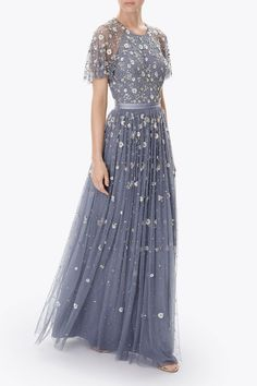 A signature style for Needle & Thread, the backless Comet Gown features all-over embellishment of iridescent sequins and silver cut beading. This stunning embellished tulle maxi dress has a pretty sleeve detail and the vintage blue shade keeps its appeal throughout the season.
