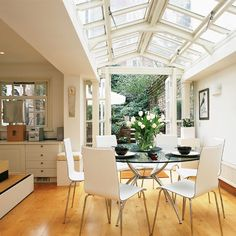 Pitched roof garden room with pine flooring, white walls and black hi-gloss dining table and white chairs