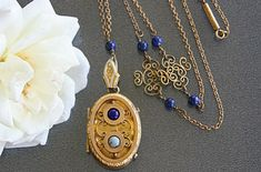 How the lapis lazuli beads on the gold chain match the bead on the locket. | 14 Vintage Locket Details That Are Utterly Delightful
