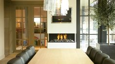 A slim line, three sided modern fireplace set against a wall installed here in a contemporary kitchen. the slim nature of this modern fireplace design means it has minimum projection. Tv Above Fireplace, Wooden Fireplace, Fireplace Tv Stand, Home Fireplace, Fireplace Remodel, Living Room With Fireplace, Fireplace Design, Wall Fireplaces, Fireplace Ideas