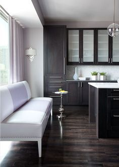  dark wood cabinetry with the grain of the wood peeking through, luxurious brown wood floors, marble island counters, a mosaic tile backsplash and some hints of lavender here and there.