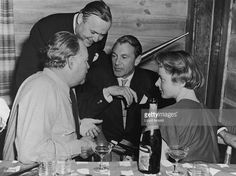 From left to right, American writer Ernest Hemingway (1899 - 1961), American film director Henry Hathaway (1898 - 1985), American actor Gary Cooper (1901 - 1961) and Swedish actor Ingrid Bergman (1915 - 1982) talk and drink at a table - Trail Creek Cabin, Ketchum, Idaho.