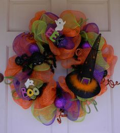 "Halloween Mesh Wreath Witch's Hat Spider - This Halloween wreath is made with orange mesh, a smaller purple and green mesh ribbon on a black wire form. Embellished with a witch's hat, black spider, sayings, purple and black ornaments. The wreath is about 26""."