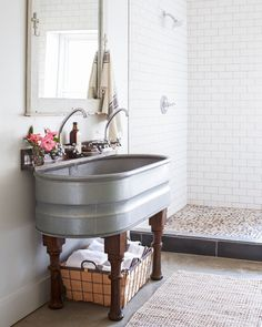 This workhorse of a sink (converted from a water trough from the Tractor Supply Company) is up for almost any chore. To add some whimsy to its streamlined silhouette, wood legs from an old table were added.   - CountryLiving.com