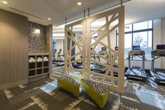 Storage and geometric screens work well to close the extended fitness area from the entrance. PARC MERIDIAN at Eisenhower Station | PARADIGM COMPANIES | ALEXANDRIA, VA  #newconstruction #interiordesign #interiorarchitecture #fitness #fitnesscenter #dividers #lighting #acoustics #refreshing #excercise #multifamily #residential