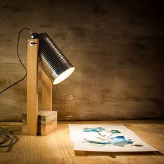 "This is a handmade wooden adjustable table lamp made of Beech wood. The lamp features a metallic ""tin"" shade and a base composed of concrete & wood."