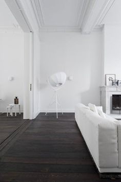 The large 'Place' sofa by Vitra is the focal point in the living where the residents of this all white house designed by Niels Maier of Studio Niels gather around the fireplace. In this historic build