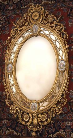 A Victorian giltwood and gilt composition mirror, by C. Nosotti, c.1870, the oval plate within a beaded and berried laurel inner frame, the border plates applied with entwined foliage and four Sevres style porcelain plaques depicting young couples