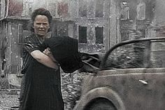 A distressed woman after a bombing raid while Wehrmacht car drives by.