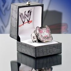Introducing the Officially Licensed WWE Divas Championship Belt Replica Finger Ring. Made by Figures Toy Company. The ring is made of brass to simulate the gold and also is finished with black hematite to simulate the belt strap. The ring has an adjustable shank that fits rings size 6 to 12 with ease. Ring will be shipped in a black jewelry box with the WWE logo printed on the inside of the box.
