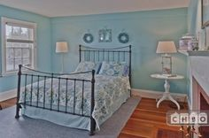 The guest bedroom of this home is in light blues, with traditionally styled furniture and a large fireplace.