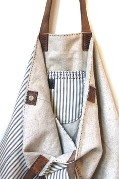Sail Away Tote Bag made of antique American ticking stripe cotton repurposed from the pioneering days, mixed with heavy duty Irish linen and aged leather straps once used to lead horses around the countryside. Patina on the old sturdy leather hand stitched with Irish linen. Two divided pockets accented with antique Japanese Indigo cotton remnants and one small pocket that sits alone on one side waiting for your modern mode of communication. Made to last.