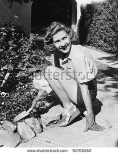 stock photo : Young woman in a garden doing gardening