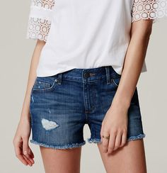 """In a distressed dark indigo wash, our cut-off denim shorts exude free-spirited cool in a flattering and comfortable way. Zip fly with button closure. Belt loops. Five-pocket styling. Tonal topstitching. Distressed detail. Frayed hems. 3"""" inseam."""