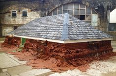 A pound of flesh for 50p by Alex Chinneck. British artist Alex Chinneck built a brick house only to watch it melt into the earth. The gloopy building, made from bricks formed of wax
