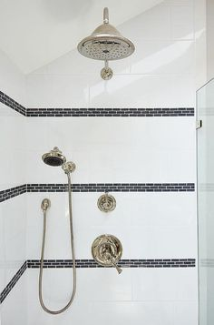 Gorgeous bathroom features a walk in shower with sloped ceiling filled with white porcelain ...