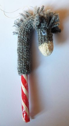 Free Knitting Pattern for Candy Cane Donkey - Candy Cane DonkeyThis clever design creates a donkey or horse head knit in the round to slip over a candy cane for ornaments or treats. To fit a 12cm candy cane. Designed by J Paling who requests that you consider donating to a donkey sanctuary.