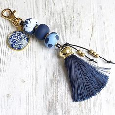 Gorgeous navy blue and gold keychain, with a lush navy blue silk tassel and pretty blue and white floral cabochon pendant. The keychain has an easy to use gold swivel clasp making it simple to attach to your keys or to a bag. The beads are made from polymer clay and each bead has been