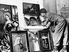 """1945 photo, republished during the 1999 Washington Conference, of U.S. soldier examining """"paintings, part of the loot gathered from all parts of Europe by Hermann Goering, in 1945 in Germany"""")"""