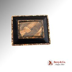 """Antique Victorian 12k gold rectangular form brooch decorated with black enamel and foliate pattern on rims. The centerpiece features two-tone plaited hair lock under glass front. The brooch has engraved monogram """"ENG"""" on back and a tiny bail, so it's possible to wear it like a pendant.  Hair jewelry was the height of the romanticism and sentiment that characterized the Victorian era. Some pieces were done as mourning pieces or """"momento mori"""" (""""remember you must die"""")."""