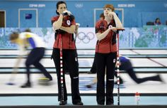 Hmmmm.... Canada's Jill Officer, left, and Dawn McEwen, right, wait on the sidelines of the ice sheet during the women's curling competition against Britain. Sochi 2014.