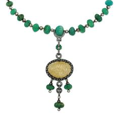 AN EMERALD, QUARTZ AND DIAMOND NECKLACE The graduated single row of carved emerald beads interspersed by rose-cut diamond single stone collets, suspending a large carved quartz pendant with rose-cut diamond frame and surmount, to a further three emerald and diamond drops, 45.8cm long