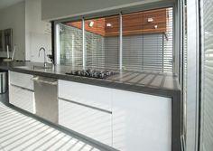 משטח ה''אי'' במטבח עשוי בטון, הארונות צבועים בצבע הקיר הלבן ודלתות מכשירי עשויות נירוסטה, במראה תעשייתי במכוון ( צילום: עמרי מירון )