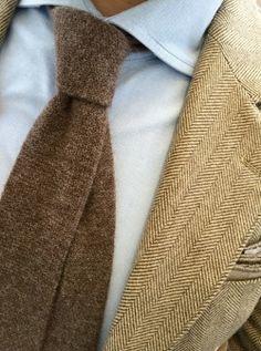 Light brown tweed jacket, light blue shirt, brown tie
