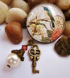 Brosche mit einer antikgoldfarbenen Fassung und einem handgearbeiteten Glas-Cabochon mit nostalgischem Vogel-Motiv. Die Perlenanhänger bestehen au...