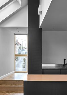 White surfaces and ceilings that reflect the pitch of the roofs enhance the feeling of height and lightness in the living areas, contrasted by dark wood flooring. British Architecture, Amazing Architecture, Wells Next The Sea, Two Bedroom House, Dark Wood Floors, Wood Flooring, House Names, Minimal Home, Zaha Hadid Architects