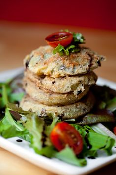 Fried Green Tomatoes – Under ripe green tomato slices, dredged in wet batter mix of egg, water and milk. Pressed into dry batter mix of corn meal, flour, salt, dried Italian seasonings and pepper.   Fried in peanut oil and stacked on baby greens with sliced cherry tomatoes. Drizzled with boiled balsamic vinegar reduction.