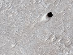 NASA's HiRISE camera is at it again. This time it's grabbed an image of the collapsed roof of a Martian lava tube that's much larger than any on Earth. Astronauts On The Moon, 8 Planets, Universe Today, Lava Flow, Ancient Aliens, The Martian, Larger, Tube, Earth