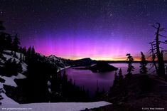 Why is this aurora strikingly pink Crater Lake in Oregon, USA. Typically, it is known, the lowest auroras appear green. These occur at about 100 kilometers high and involve atmospheric oxygen atoms excited by fast moving plasma from space. The next highest auroras-at about 200 kilometers up appear red, and are also emitted by resettling atmospheric oxygen. Some of the highest auroras visible-as high as 500 kilometers up-appear blue, and are caused by sunlight-scattering nitrogen ions.