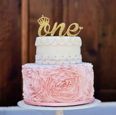 """I'm thinking of having the cake be the bottom layer of this but white. I have a gold glitter """"One"""" to add on top. Maybe a real little pink flower or two next to it?"""