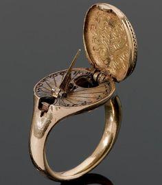 Anillo de oro de 1570, incluye  reloj de sol y brújula. Posiblemente alemán. Grabado con un escudo de armas. Dimensiones de 1.8 x 2.0 cm.