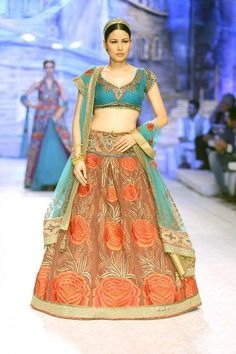 Model walks the ramp in orange lehnga and blue choli designed by fashion designer J J Valaya. Valaya's collection, 'The Maharaja Of Madrid' and ramp set-up brought alive the old world charm of India and Spain. From Aamby Valley India Bridal Fashion Week. #Bollywood #Fashion