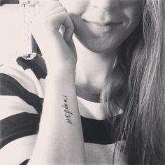 Chica con un tatuaje de la frase meraki en si brazo